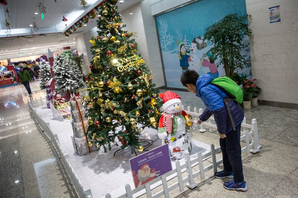 epa06404010 A Chinese young boy looks at a Christmas tree at a shopping mall in Beijing, China, 23 December 2017. While Christmas is not celebrated by most Chinese in the secular China, Christmas lights and decorations still adorn most shopping malls during the festive season to bring much cheer to the retail scene.  EPA/ROMAN PILIPEY