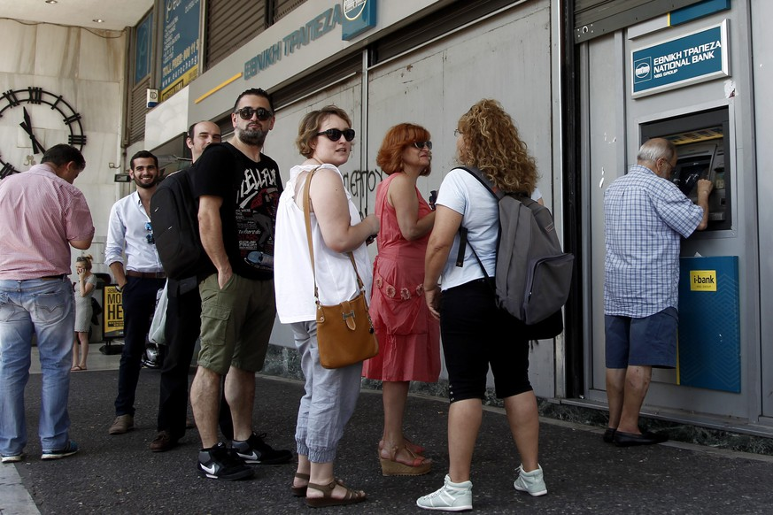 epa04833647 People queue to withdraw money from an ATM outside a branch of Greece's National Bank in Athens, Greece, 06 July 2015. Prime Minister Alexis Tsipras has called on the political leaders to assist the government and support the clear and explicit mandate of the Greek people in 05 July referendum for a sustainable solution, according to government source.  EPA/ALEXANDROS VLACHOS