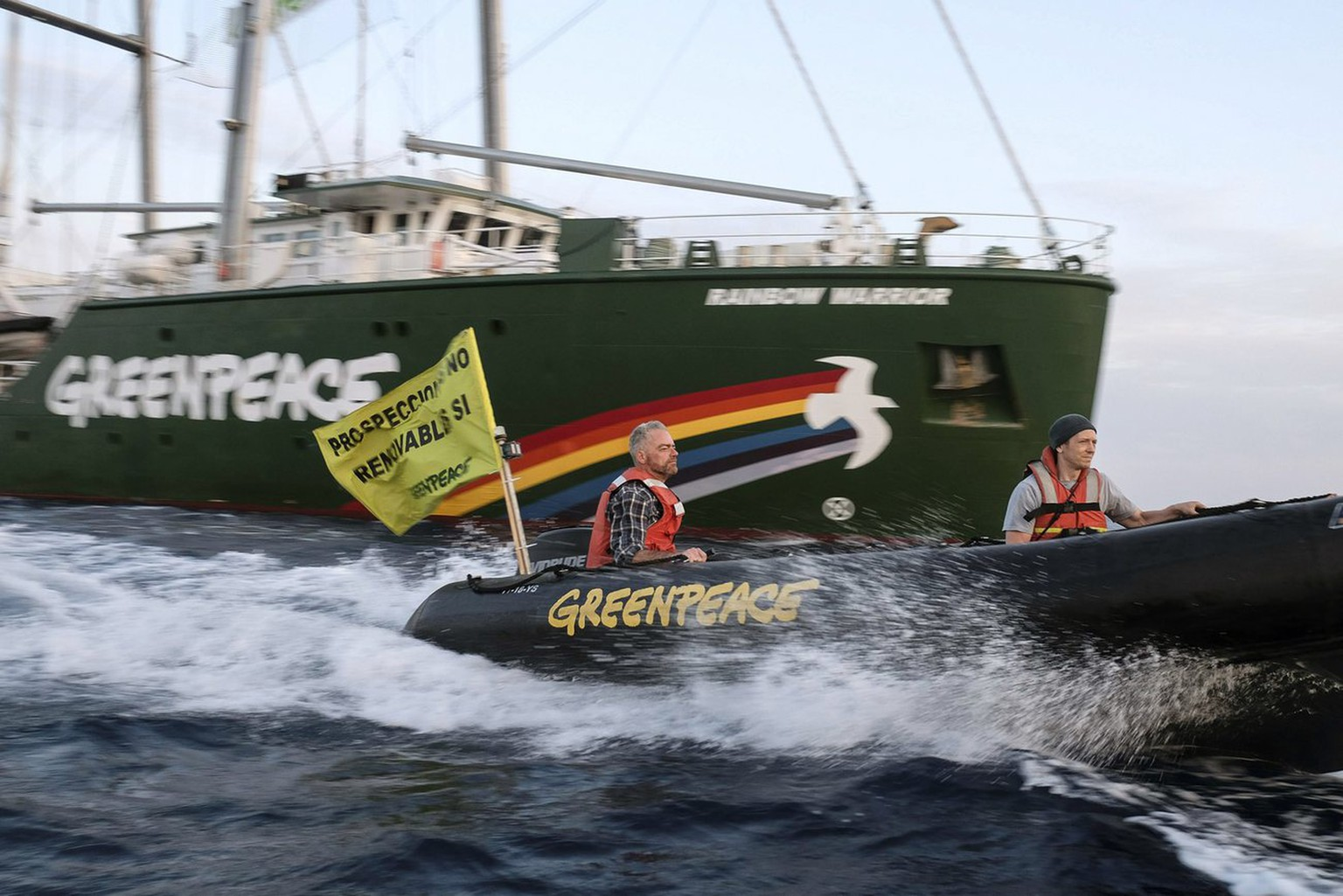 epa04249397 A handout picture released by Greenpeace shows Greenpeace activists at sea on board of a raft from the Rainbow Warrior ship (back) deployed at an oil retaining barrier, 100 metres off the Es Vedra small rocky island's natural reserve, south western Ibiza, eastern Spain, 11 June 2014. The action was held to raise public's awareness of planned oil drillings in Balearic Islands waters. Greenpeace activists unfoled a 144-metre banner reading 'No Oil' (unseen).  EPA/PEDRO ARMESTRE/GREENPEACE  HANDOUT EDITORIAL USE ONLY/NO SALES/NO ARCHIVES