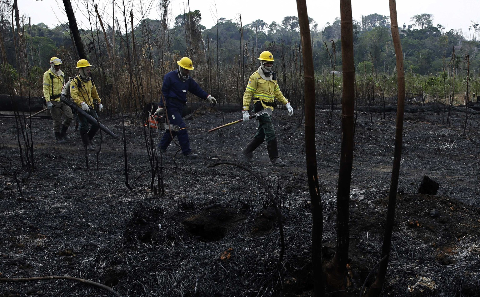 Firefighters walk across charred land to another area as they work to put out fires in the Vila Nova Samuel region, along the road to Jacunda National Forest near the city of Porto Velho in Rondonia state, part of Brazil's Amazon, Sunday, Aug. 25, 2019. Leaders of the Group of Seven nations said Sunday they were preparing to help Brazil fight the fires burning across the Amazon rainforest and repair the damage even as tens of thousands of soldiers were being deployed to fight the blazes that have caused global alarm. (AP Photo/Eraldo Peres)