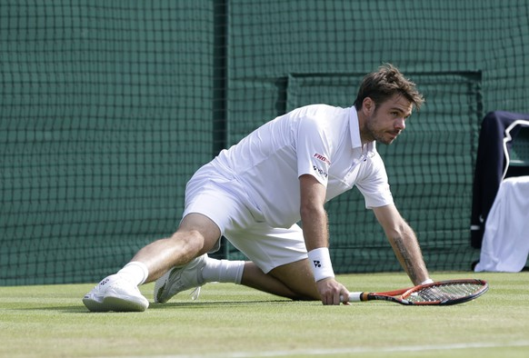 Stan Wawrinka of Switzerland looks up after falling to the ground as plays Richard Gasquet of France during the men's quarterfinal singles match at the All England Lawn Tennis Championships in Wimbledon, London, Wednesday July 8, 2015. (AP Photo/Pavel Golovkin)