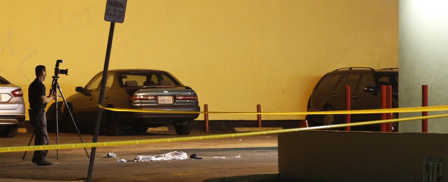A Los Angeles County Sheriff's Department investigator photographs the scene of an accident at a parking lot in Compton, Calif., Thursday, Jan. 29, 2015. A lawyer for Marion