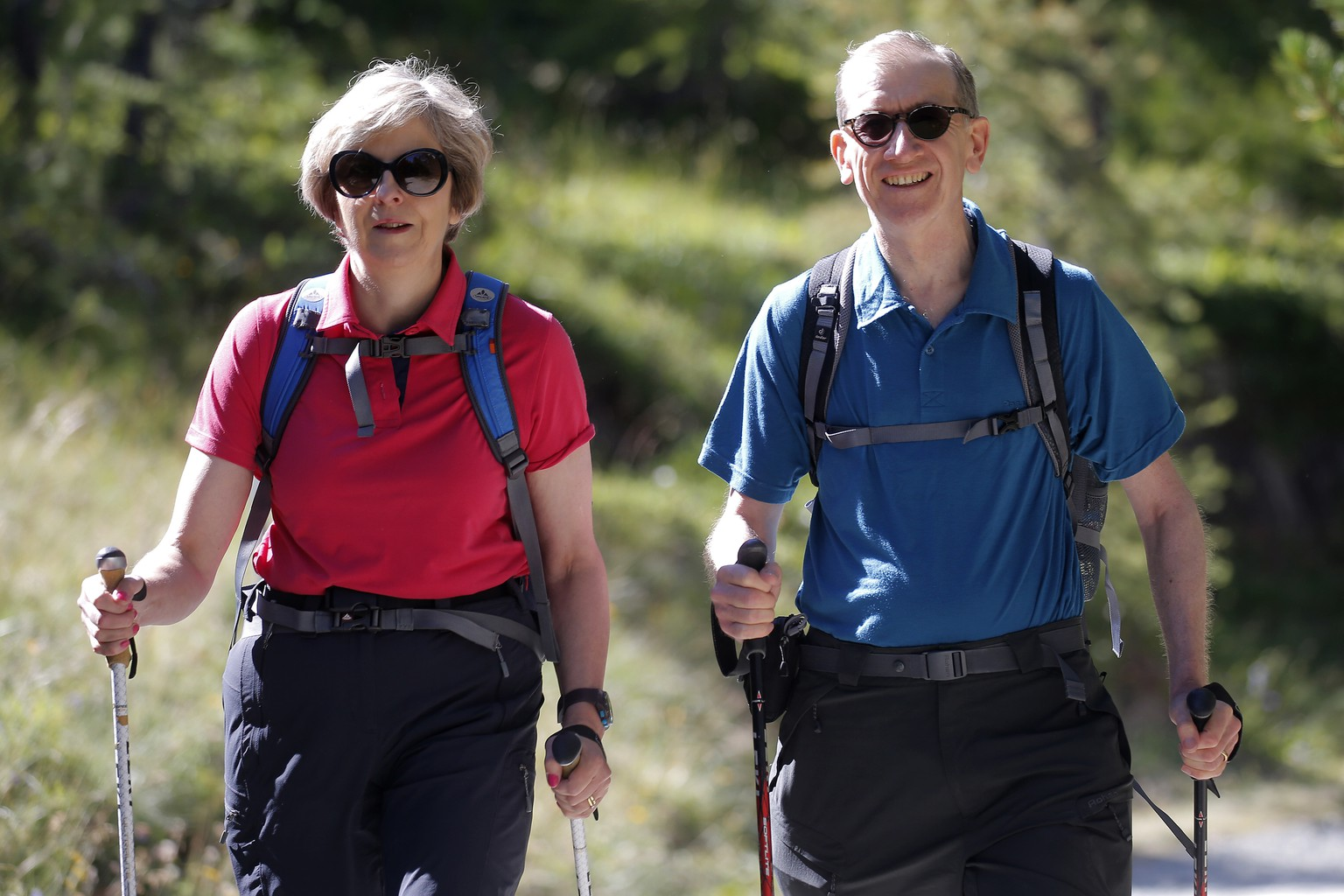 British Prime Minister Theresa May, walks in a forest with her husband Philip  at the start of a summer holiday in the Alps in Switzerland on Friday Aug. 12, 2016. (Marco Bertorello/Pool via AP)