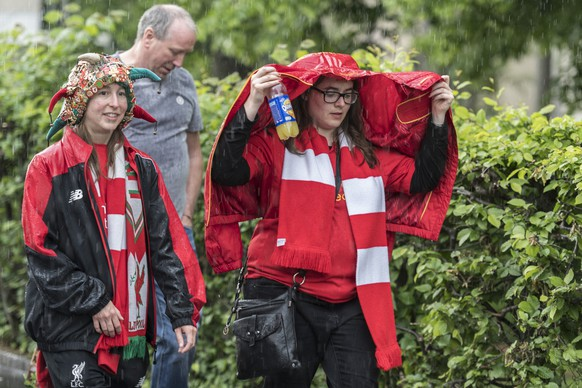 Fans of Liverpool shield themselves from the starting rain as they near the stadium ahead of the UEFA Europa League final between England's Liverpool FC and Spain's Sevilla Futbol Club in Basel, Switzerland, Wednesday, May 18, 2016. (KEYSTONE/Manuel Lopez)