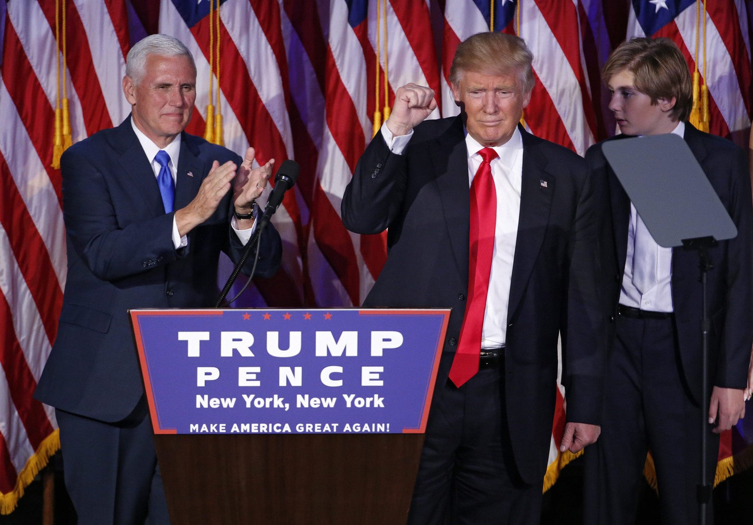 epa05623720 US Republican presidential nominee Donald Trump (C) waves next to running mate Mike Pence (L) as he delivers a speech on stage at Donald Trump's 2016 US presidential Election Night event as votes continue to be counted at the New York Hilton Midtown in New York, New York, USA, 08 November 2016.  EPA/SHAWN THEW