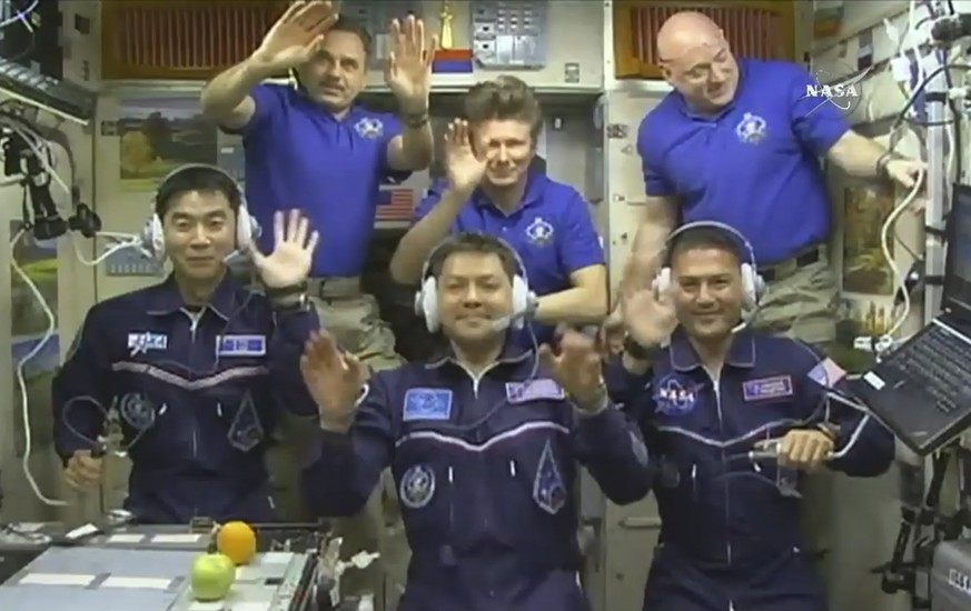 In this image taken from video from NASA, astronauts, front row from left, Kimiya Yui, of Japan, Oleg Kononenko, of Russia, and Kjell Lindgren, of the United States, wave after they boarded the International Space Station, early Thursday, July 23, 2015. Joining the new crew are, rear row from left, astronauts Mikhail Kornienko and Gennady Padalka, from Russia, and Scott Kelly, of the U.S. (NASA via AP)