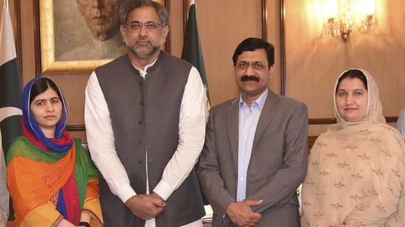 In this photo released by the Press Information Department, Pakistani Nobel Peace Prize winner Malala Yousafzai, left, and her parents pose for a photograph with Shahid Khaqan Abbasi, second from left, Prime Minister of Pakistan in Islamabad, Pakistan, Thursday, March 29, 2018. Yousafzai on Thursday said she was excited to be back in Pakistan for the first time since she was shot in 2012 by Taliban militants angered at her championing of education for girls. (Press Information Department via AP)