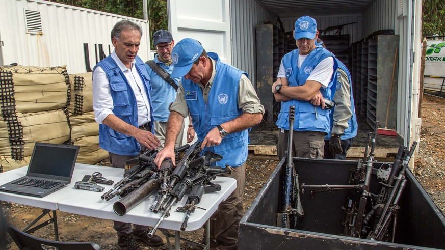 epa06026973 A handout photo made available by the Revolutionary Armed Forces of Colombia (FARC) shows Chief of United Nations Mission in Colombia Jean Arnault (L) and other UN members during an inspection of FARC weapons at La Elvira, Colombia, 13 June 2017. Revolutionary Armed Forces of Colombia (FARC) began the delivery of a second batch of weapons constituting 30% of its arsenal to the UN Mission in the rural area of La Elvira in the department of Cauca in the southwest.  EPA/FARC HANDOUT  HANDOUT EDITORIAL USE ONLY/NO SALES