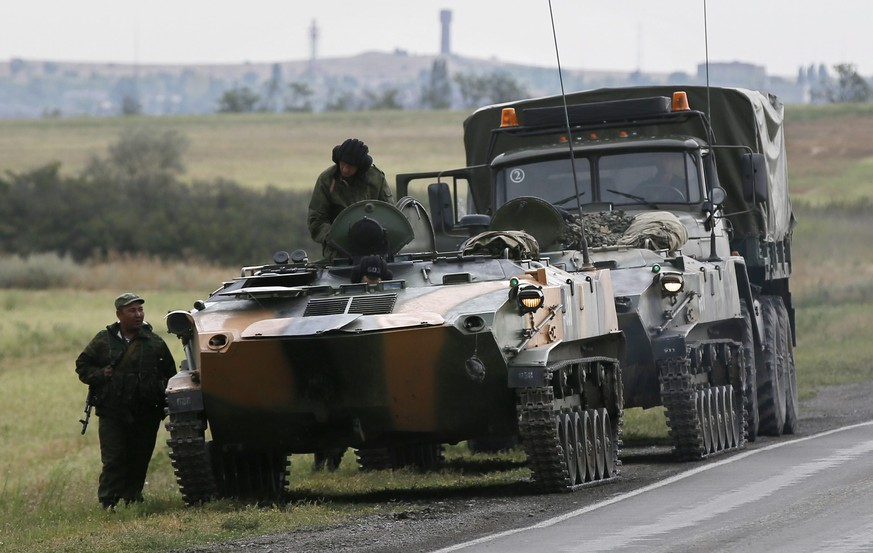 epa04359025 Russian military vehicles and servicemen in a field outside the town of Kamensk-Shakhtinsky in Rostov region, about 30 kms from the Russian-Ukrainian border, Russia, 18 August 2014. A convoy of almost 280 lorries has been standing at the Russian-Ukrainian border since 14 August. Ukraine said that it would recognize the convoy as humanitarian if it was delivered by the International Committee of the Red Cross (ICRC). However, the ICRC has said that it still needed security guarantees to pass through territory held by pro-Russian separatists.  EPA/YURI KOCHETKOV