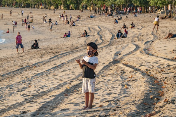 epa08559729 A boy wearing a protective face mask plays on Kuta Beach amid coronavirus pandemic in Kuta, Bali, Indonesia, 03 July 2020. (issued 22 July 2020) The country reported its first case of COVID-19 on Mar. 2, about a month and a half after the first case outside of China was reported in Thailand on Jan. 13. Now it has the most infections in all of Southeast Asia with over 89,869 confirmed cases and more than 4,320 deaths. It is believed that more than 200 Indonesian children have died due to the infectious disease. At least 1,543 children have tested positive for COVID-19 and 36 have died, while 204 out of more than 6,000 under surveillance (suspected cases) have died, the Jakarta Post reported, citing Indonesian Pediatric Society data from June 25.  EPA/MADE NAGI  ATTENTION: This Image is part of a PHOTO SET