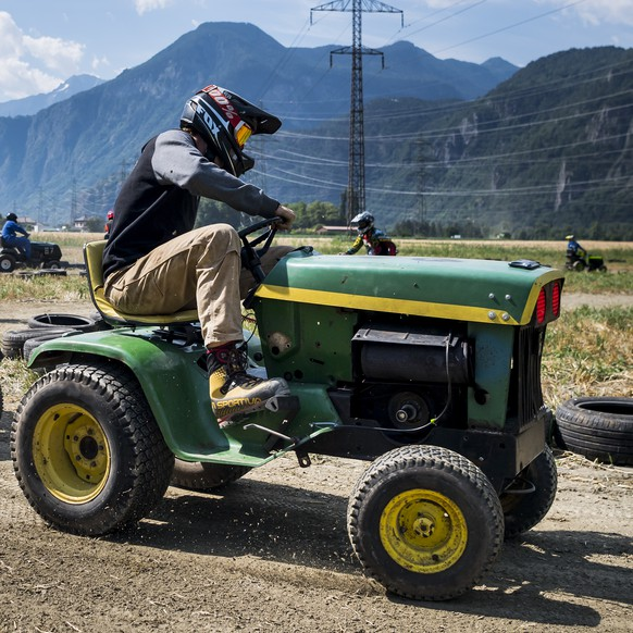 Drivers compete during the fifth edition of the motorized lawn movers race in Dorenaz, Switzerland, Saturday, July 14, 2018. About 23 motorized lawn mowers compete on a one kilometer-long course during a competition split in two three-hours-long races. (KEYSTONE/Jean-Christophe Bott)...Des participants en action lors de la 5eme edition de la course de tondeuses a gazon ce samedi 14 juillet 2018 a Dorenaz en Valais. 23 tondeuses a gazon concourent sur un parcours de plus d'un kilometre, lors de deux courses de trois heures. (KEYSTONE/Jean-Christophe Bott)