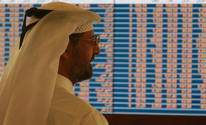 A trader watches an electronic share price display at the Doha Stock Exchange in Doha May 28, 2015. Qatar's bourse fell in early trade on Thursday, extending losses following the launch of criminal investigations against senior FIFA officials, while stocks upgraded by index compiler MSCI supported markets in the United Arab Emirates. REUTERS/Naseem Zeitoon