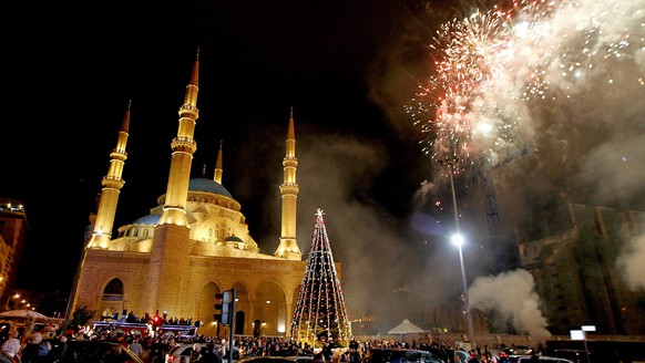 epa04536349 Fireworks explode over a giant Christmas tree, next to Al-Amin Mosque during the event 'Beirut Christmas carnival' organized by Beirut municipality in Beirut, Lebanon, 20 December 2014. Beirut is one of the most religiously diverse cities of the Middle East with big Christians and Muslim communities.  EPA/NABIL MOUNZER