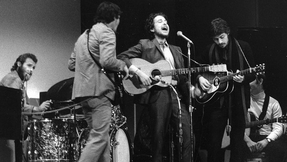 "FILE - In this Jan. 20, 1968 file photo, folk singer Bob Dylan, center, performs with drummer Levon Helm, left, Rick Danko, second left, and Robbie Robertson of The Band at Carnegie Hall in New York. For most of 1967, Bob Dylan quietly made history in a basement outside of Woodstock, New York. With the gifted musicians who later named themselves Band, he sang dozens of old country and Appalachian ballads, along with such originals as ""I Shall Be Released"" and ""Tears of Rage.""  (AP Photo, File)"
