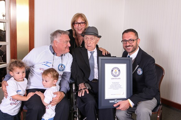 In this photo supplied by the Guinness World Records, Marco Frigatti, Head of Records for Guinness World Records, right, poses with Israel Kristal, second right, as he presents a certificate for being the oldest living man, in Haifa, Israel. Guinness said in a statement that Kristal is 112 years and 178 days old as of March 11. Kristal is seen with some of his family members, from left to right, grandchildren Nevo and Omer, son Heim Kristal, and daughter Shula Kuperstoch. (Dvir Rosen/Guinness World Records via AP)