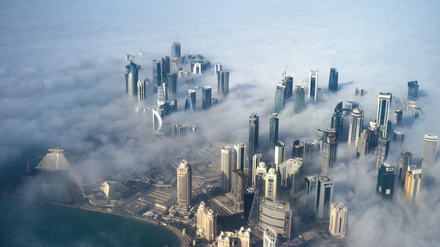 epa06052579 (FILE) - An aerial view of high-rise buildings emerging through fog covering the skyline of Doha, as the sun rises over the city, in Doha, Qatar, 15 February 2014 (reissued 27 June 2017). The report by then FIFA chief ethics investigator Michael J. Garcia on Qatar's successful FIFA World Cup 2022 bid has been leaked after German newspaper Bild published details on 27 June 2017, surfacing new corruption claims against the 2010 bidding contest.  EPA/YOAN VALAT