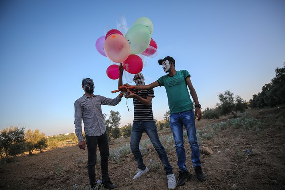 epa08599709 Palestinians wearing masks prepare to attach an incendiary device to balloons before realeasing them to Israeli lands near the border between Israel and Eastern Gaza Strip, Gaza Strip, 12 August 2020.  EPA/MOHAMMED SABER