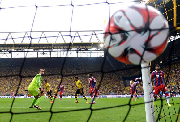 DORTMUND, GERMANY - AUGUST 13:  Goalkeeper Manuel Neuer (L) of Munich looks on as Henrikh Mkhitaryan (2nd L) of Dortmund scores the opening goal during the DFL Supercup between Borrussia Dortmund and FC Bayern Muenchen at Signal Iduna Park on August 13, 2014 in Dortmund, Germany.  (Photo by Lars Baron/Bongarts/Getty Images)