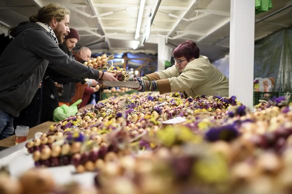 """Personen kaufen die Zwiebelzoepfe, waehrend dem traditionellen """"Zibelemaerit"""", am Montag, 25. November 2019, in Bern. Der Zibelemaerit findet jeweils am vierten Montag im November statt. Er geht auf das 19. Jahrhundert zurueck, als Baeuerinnen aus dem Seeland und dem Freiburgischen ihr Gemuese nach Bern zu verkaufen begannen, dies jeweils waehrend zwei Wochen ab dem Martinstag. (KEYSTONE/Anthony Anex)"""
