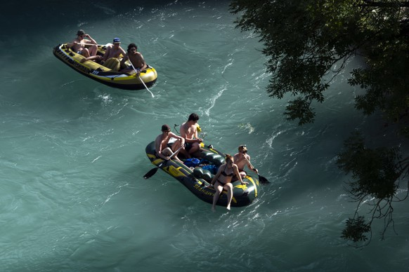 People on two inflatable boats enjoy the sun in the Aare River during the sunny and warm weather, in Bern. Switzerland, Wednesday, June 26, 2019. The forecasts predict hot weather in Switzerland with the maximum temperature at 38 degrees Celsius. (KEYSTONE/Anthony Anex)
