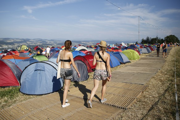 epa04849508 Festival visitors walk through the camping area at the Gurten music open air festival in Bern, Switzerland, 16 July 2015.  EPA/PETER KLAUNZER