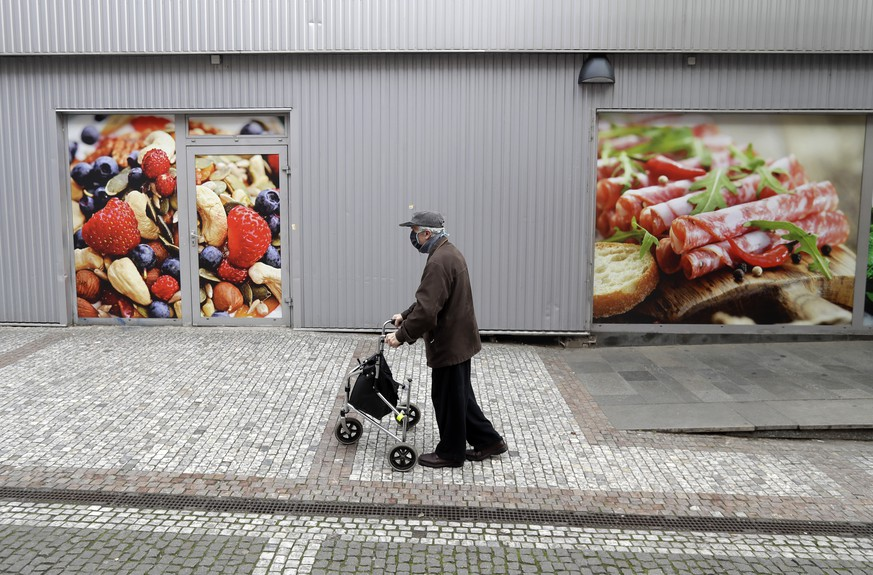 An elderly man walks to do his shopping at a grocery store in Prague, Czech Republic, Thursday, March 19, 2020. Due to the spread of the novel coronavirus called COVID-19 only people older than 65 years are allowed to grocery stores and pharmacies between 10-12 am in the Czech Republic. (AP Photo/Petr David Josek)
