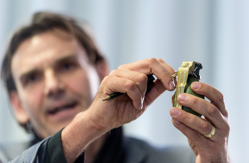 epa05133657 Chief Director Andreas Stenger of the Baden-Wuerttemberg State Criminal Office shows a model of the M52 hand grenade from former Yugoslavia during a press conference in Villingen-Schwenningen, Germany, 29 January 2016.  A hand grenade of this model was thrown onto the grounds of the shelter in an alleged attack the night before. Security personnel found the grenade which didn't explode even though the safety pin had been removed. The culprits remain unknown.  EPA/PATRICK SEEGER
