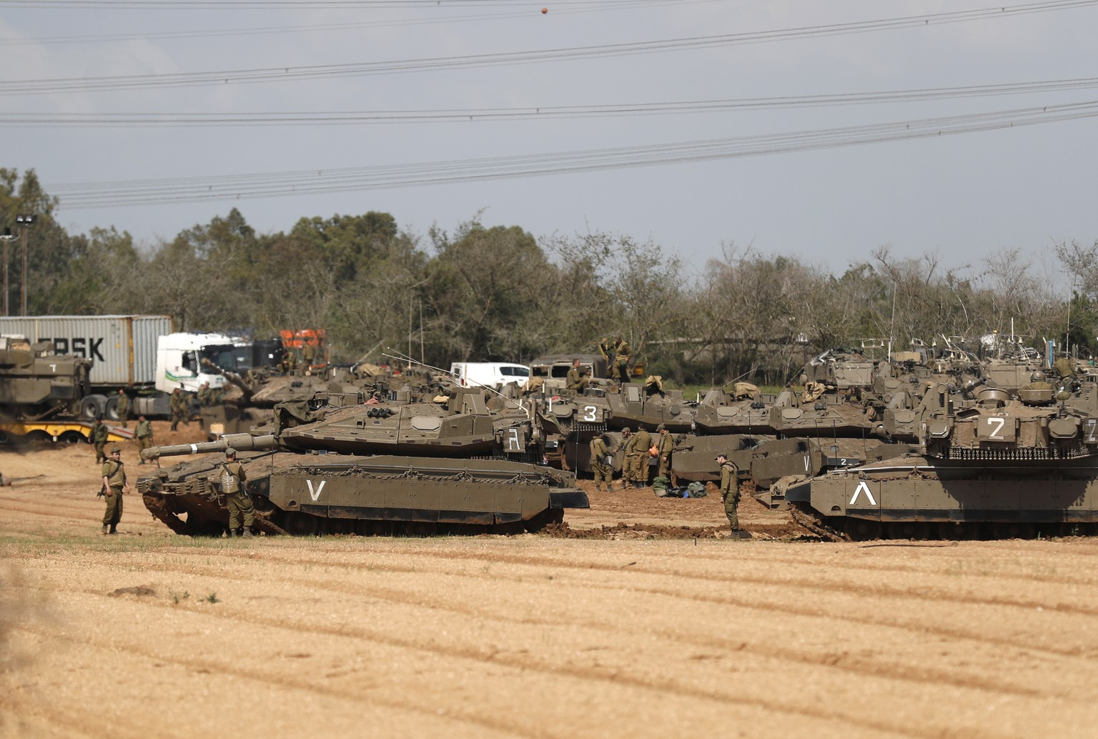 epa07464677 Israeli soldiers stand near their Merkava tanks and APCs, at a gathering point next to the border with Gaza, 26 March 2019. Israeli army is targeting Hamas militant installations in the Gaza Strip in response to a rocket fired from Gaza Strip that hit a house in central Israel.  EPA/ATEF SAFADI