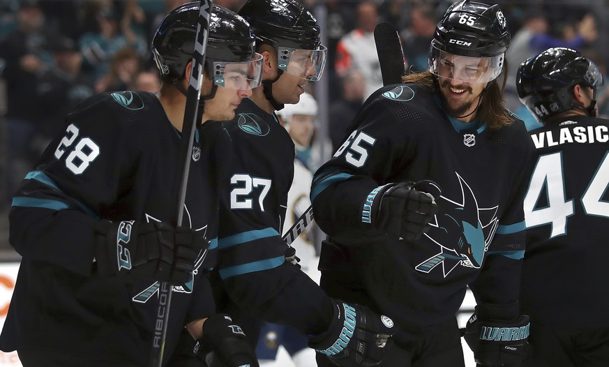 San Jose Sharks' Joonas Donskoi (27) celebrates with Timo Meier, left, and Erik Karlsson (65) after scoring a goal against the Buffalo Sabres during the first period of an NHL hockey game Thursday, Oct. 18, 2018, in San Jose, Calif. (AP Photo/Ben Margot)