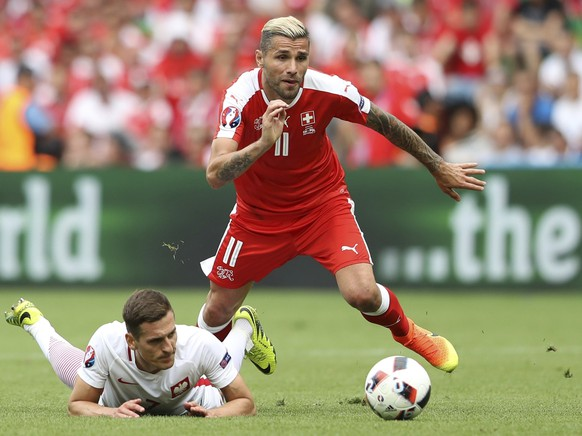 FILE - In this Saturday, June 25, 2016 file photo, Switzerland's Valon Behrami, right, gets the ball past Poland's Arkadiusz Milikduring the Euro 2016 round of 16 soccer match between Switzerland and Poland, at the Geoffroy Guichard stadium in Saint-Etienne, France. (AP Photo/Laurent Cipriani, File)