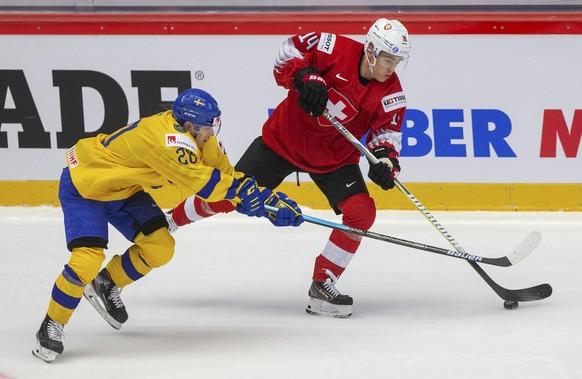 Sweden's Nicola Pasic, left, and Switzerland's Sandro Schmid in action during the 2020 IIHF World Junior Ice Hockey Championships Group A match between Switzerland and Sweden in Trinec, Czech Republic, Saturday Dec. 28, 2019. (Vladimir Prycek/CTK via AP)