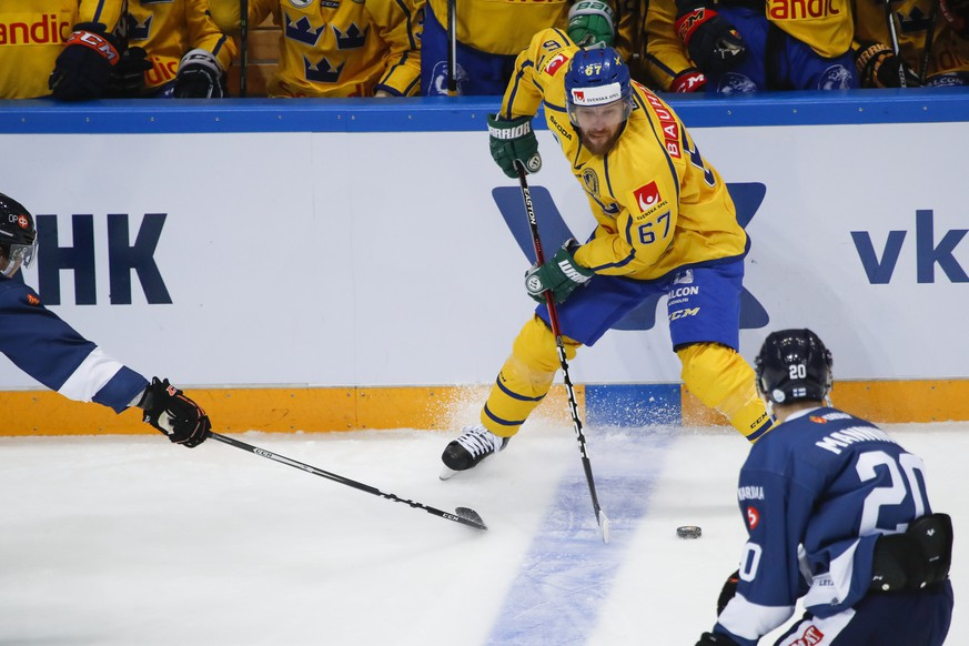 Sweden's Linus Omark, center, controls the puck during the Ice Hockey Channel One Cup match between Finland and Sweden in Moscow, Russia, Saturday, Dec. 17, 2016. (AP Photo/Pavel Golovkin)