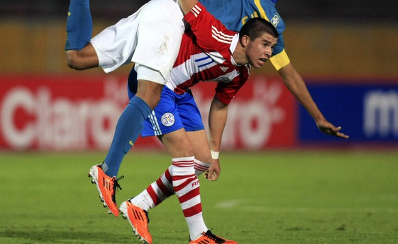 Brazil's Marquinhos, top, fights for the ball with Paraguay's Mauro Caballero during a South American U-17 soccer match in Quito, Ecuador, Wednesday, April 6, 2011. (AP Photo/Dolores Ochoa)