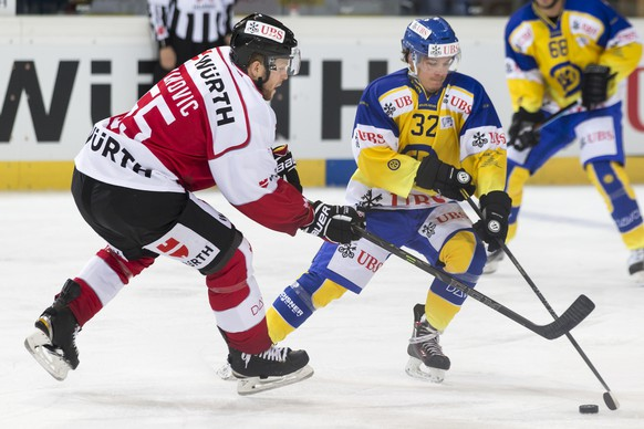 Team Canada's Daniel Vukovic, left, fight for the puck with Davos' Sin Schlaepfer during the game between Team Canada and Switzerland's HC Davos at the 89th Spengler Cup ice hockey tournament in Davos, Switzerland, Monday, December 28, 2015. (KEYSTONE/Pascal Muller)