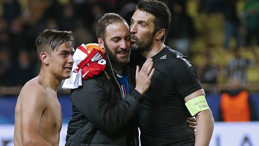 epa05942703 Juventus goalkeeper Gianluigi Buffon (R) hugs his teammate Gonzalo Higuain (C) net to Paulo Dybala (L) after winning the UEFA Champions League semi final, first leg soccer match between AS Monaco and Juventus at Stade Louis II in Monaco, 03 May 2017.  EPA/GUILLAUME HORCAJUELO