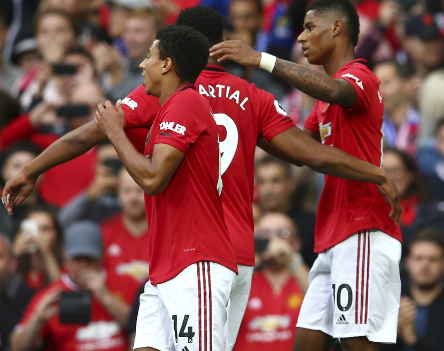 Manchester United's Marcus Rashford, right, celebrates with teammates after scoring his sides first goal during the English Premier League soccer match between Manchester United and Chelsea at Old Trafford in Manchester, England, Sunday, Aug. 11, 2019. (AP Photo/Dave Thompson)