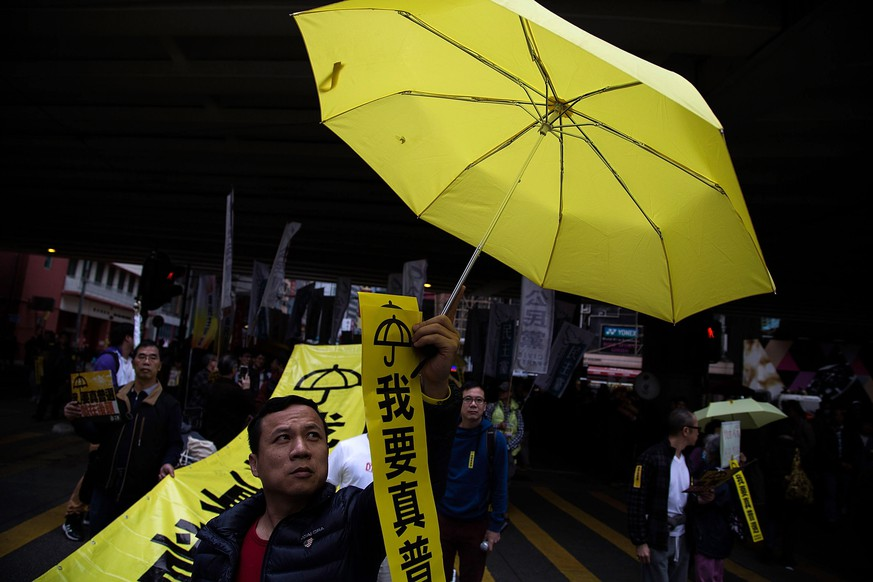 HONG KONG - FEBRUARY 01:  A man holds a yellow umbrella during tens of thousands of protesters called for real universal suffrageduring a march for democracy on February 1, 2015 in Hong Kong, Hong Kong. Pro-democracy supporters gather in Hong Kong for the first major rally since the occupy movement took over parts of Hong Kong, in a standoff that lasted over 2 months. Protestors are calling for autonomy in Hong Kong elections as China continues to have control over who can run for the position.  (Photo by Lam Yik Fei/Getty Images)