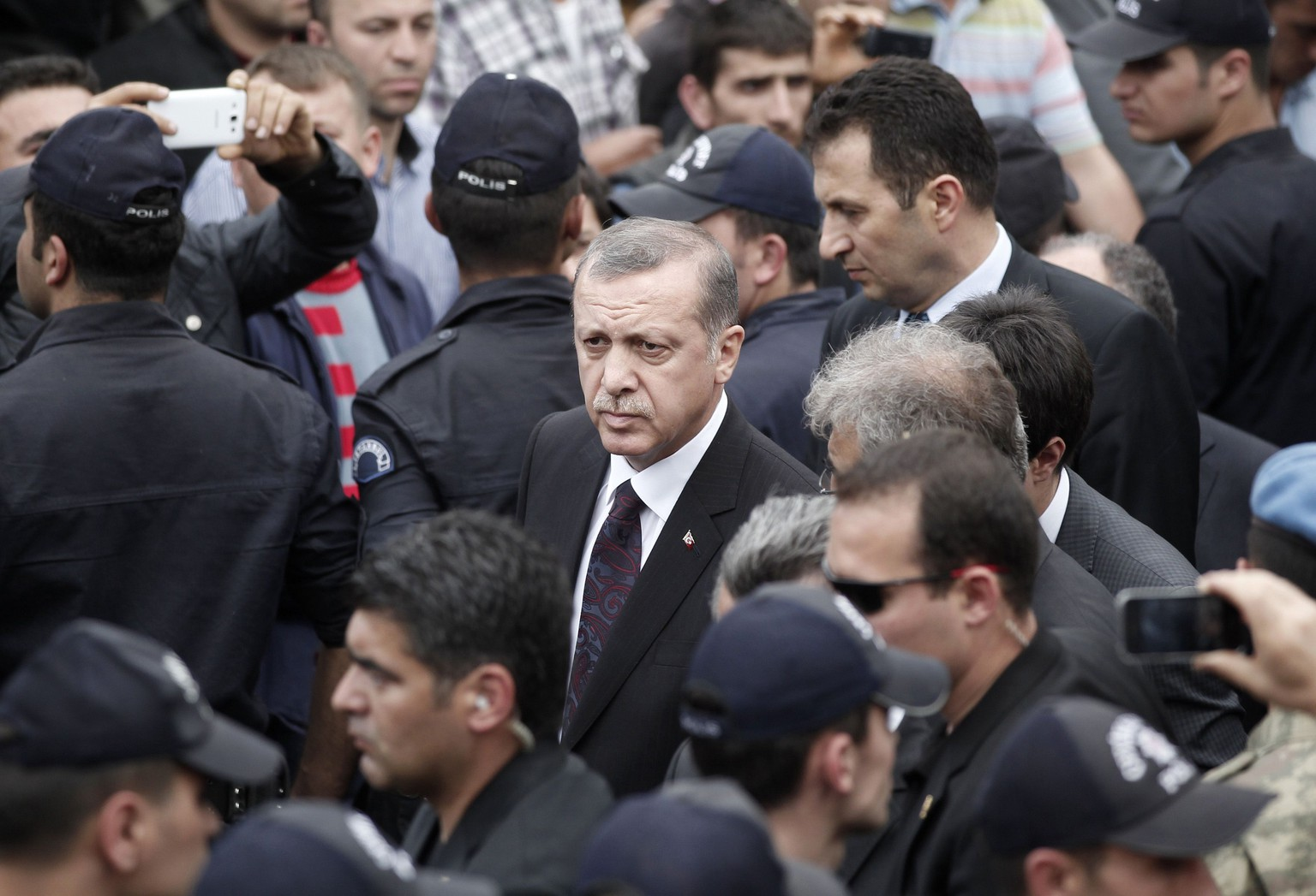 Turkey's Prime Minister Tayyip Erdogan (C) walks during his visit to Soma, a district in Turkey's western province of Manisa, after a coal mine explosion May 14, 2014. Rescuers pulled more dead and injured from the coal mine in western Turkey on Wednesday more than 19 hours after the explosion, bringing the death toll to 205 in what could become the nation's worst ever mining disaster. Hundreds more were still believed to be trapped in the mine in Soma, about 480 kilometres (298 miles) southwest of Istanbul. The explosion, which triggered a fire, occurred shortly after 3 pm (1200 GMT) on Tuesday. REUTERS/ Osman Orsal (TURKEY - Tags: DISASTER POLITICS)