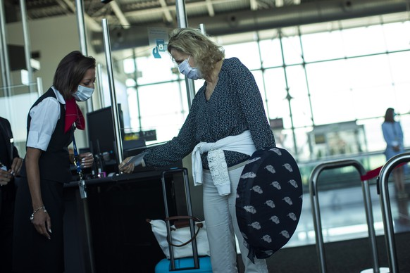 A passenger, wearing a face mask to protect against the spread of coronavirus, prepares to board a plane departing to Marseille at the Zaventem international airport during the partial lifting of coronavirus COVID-19 lockdown regulations in Brussels, Monday, June 15, 2020. Borders opened up across Europe on Monday after three months of coronavirus closures that began chaotically in March. (AP Photo/Francisco Seco)