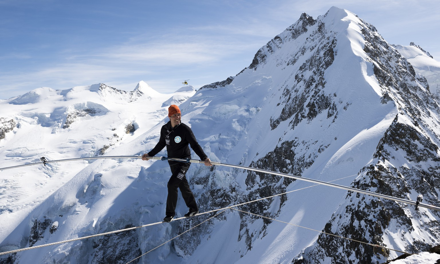 Swiss tightrope artist Freddy Nock walks on a rope towards Piz Prievlus, with the Piz Bernina and Biancograt ridge in the background, in Graubuenden, eastern Switzerland, on Friday, March 20th, 2015. He covered 350 meters of distance in an altitude of 3500 meters. (KEYSTONE/Gian Ehrenzeller)