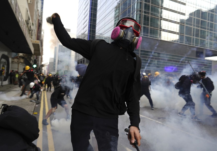A protestor hurls an object as police and demonstrators clash during a protest in Hong Kong, Saturday, Aug. 24, 2019. Hong Kong protesters skirmished with police on Saturday as chaotic scenes returned to the summer-long protests for the first time in more than a week. (AP Photo/Vincent Yu)