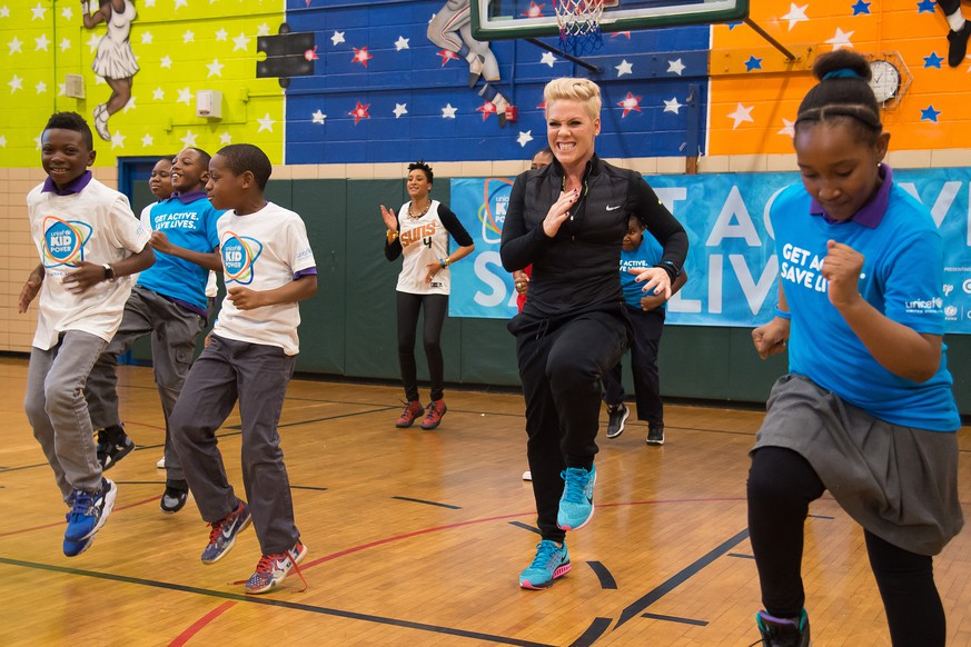 Singer Pink exercises with students from PS 242 Young Diplomats Magnet Academy at the launch of UNICEF Kid Power on Monday, Nov. 30, 2015, in New York. (Photo by Charles Sykes/Invision/AP)