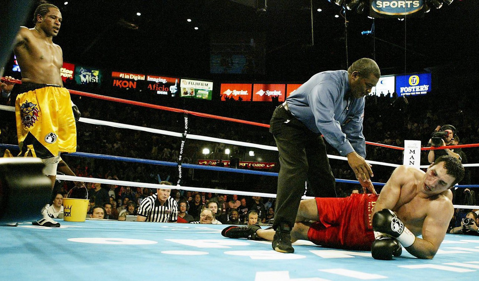 American Lamon Brewster (L) awaits the outcome as Wladimir Klitschko of the Ukraine  lies on the canvas as referee Robert Byrd starts the count in fifth round of their WBO Heavyweight Championship bout in Las Vegas, Saturday 10 April 2004. The fight was stopped as Brewster won by TKO. (KEYSTONE/EPA/BRENDAN MCDERMID)