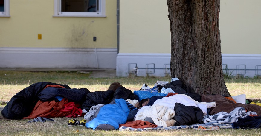 epa04876064 A photograph made available on 07 August 2015 showing asylum seekers sleeping outside on the ground at the refugee reception centre in Traiskirchen, Austria, 31 July 2015. Traiskirchen one of the largest migrant centres in Austria is now closed to new arrivals after the facility which was designed for up to 1,800 people and is now coping with 4,500 people at the camp south of Vienna.  EPA/ROLAND SCHLAGER