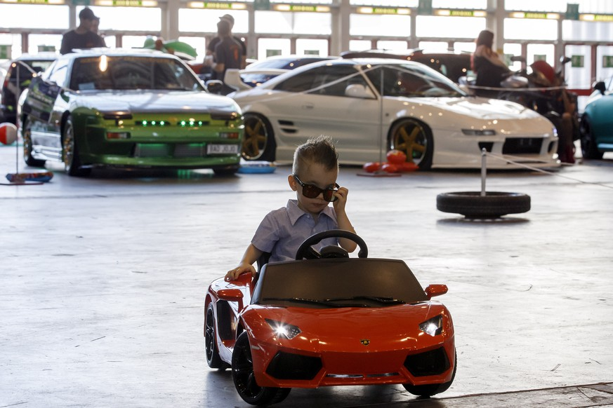 A kid drives around one of the tuned cars, during the Swiss Car Event, in Palexpo, in Geneva, Switzerland, Sunday, June 11, 2017. (KEYSTONE/Salvatore Di Nolfi)
