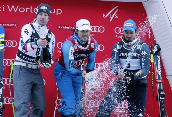 Norway's Kjetil Jansrud, center, winner of an alpine ski, men's World Cup Super G race, celebrates on the podium with second-placed Austria's Hannes Reichelt and third-placed Italy's Dominik Paris, in Santa Caterina, Italy, Tuesday, Dec. 27, 2016. (AP Photo/Marco Trovati)