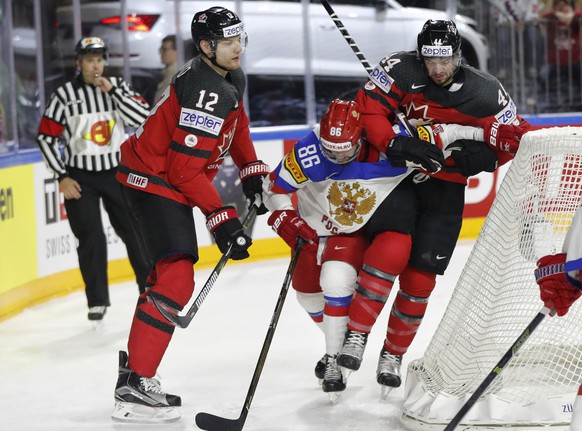 Canada's Colton Parayko, left, and Marc-Edouard Vlasic, right, tackle Russia's Nikita Kucherov at the Ice Hockey World Championships semifinal match between Canada and Russia in the LANXESS arena in Cologne, Germany, Saturday, May 20, 2017. (AP Photo/Petr David Josek)