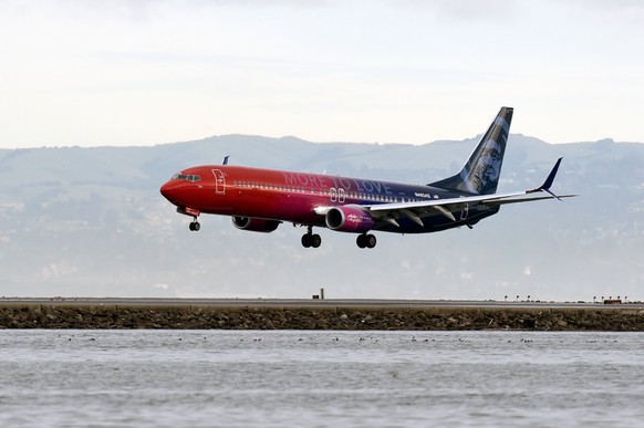 """A specially painted, co-branded Alaska Airlines and Virgin America 737-900ER aircraft, painted in shimmering red, purple and blue and featuring the slogan """"More to love,"""" lands at San Francisco International Airport, California, U.S., December 14, 2016. The newly painted aircraft is part of the merger celebration of Alaska Airlines and Virgin America.   Courtesy Bob Riha, Jr./Alaska Airlines/Handout via REUTERS   ATTENTION EDITORS - THIS IMAGE WAS PROVIDED BY A THIRD PARTY. EDITORIAL USE ONLY. NO RESALES. NO ARCHIVE."""