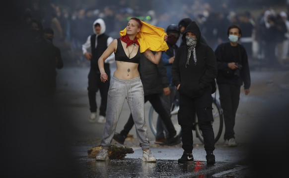 """A woman demonstrates at the Bois de la Cambre park during a party called """"La Boum 2"""" in Brussels, Saturday, May 1, 2021. A few thousand people gathered for an illegal party in a Brussels park Saturday to protest COVID-19 restrictions, only to be met with a big police force who used a water cannon and tear gas to disperse the crowd. It was the second such open-air gathering in a month. (AP Photo/Olivier Matthys)"""