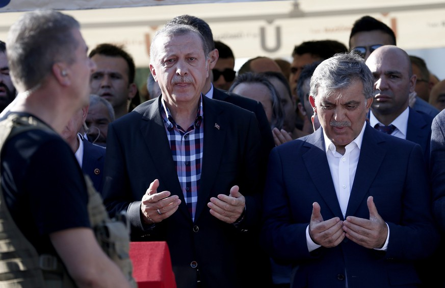 epa05429408 Turkish President Recep Tayyip Erdogan  (L) and former president Abdullah Gul (R) pray near by coffins of Erol Olcok and his son Abdullah Tayyip Olcok, who were killed in a coup attempt on 16 July, during the funeral, in Istanbul, Turkey, 17 July 2016. Turkish Prime Minister Yildirim reportedly said that the Turkish military was involved in an attempted coup d'etat. Turkish President Recep Tayyip Erdogan has denounced the coup attempt as an 'act of treason' and insisted his government remains in charge. Some 104 coup plotters were killed, 90 people - 41 of them police and 47 are civilians - 'fell martrys', after an attempt to bring down the Turkish government, the acting army chief General Umit Dundar said in a televised appearance.  EPA/SEDAT SUNA